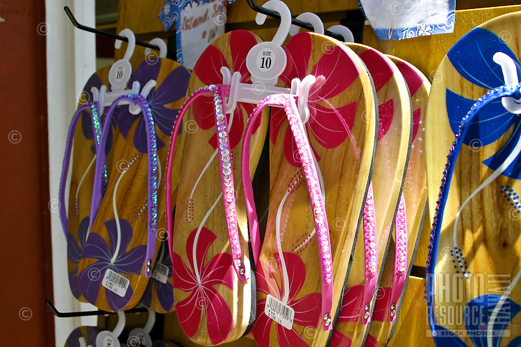 Flowery disigned sandals (flip flops) await  tourist shoppers at a local gift shop. Oahu