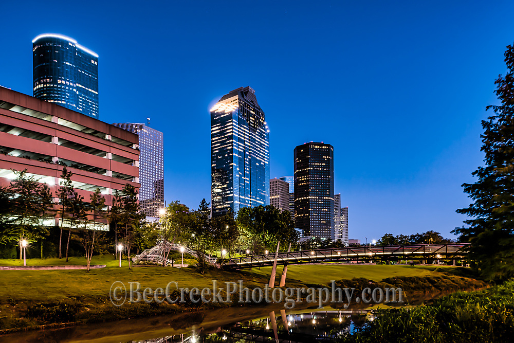 We took this from a different location so we could get some of the Buffalo Bayou in the scene.  We like the look of the Bagby to Sabine  promenade pedestrian bridge with the light on over the bayou and the Houston skyline in this image.