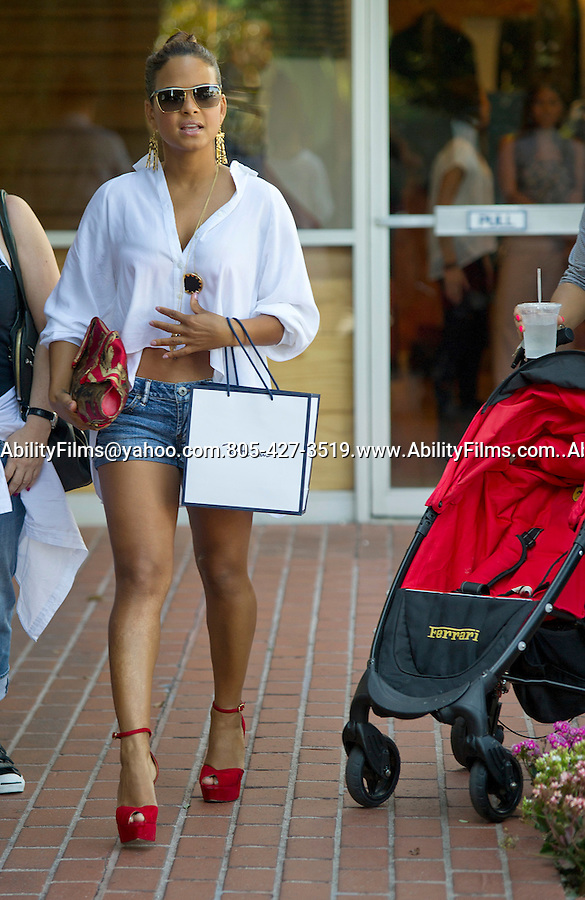 August 30th 2011...Christina Milian pregnant shopping at Fred Segal in West Hillywood smiling with her hair up in a bun red high heel shoes short daisy dukes gold necklace and earrings carrying a red skull purse ..AbilityFilms@yahoo.com.805-427-3519.www.AbilityFilms.com..