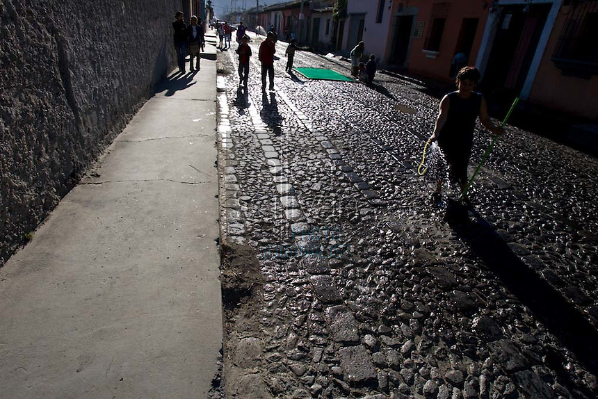 People water down a dusty cobblestone street as they make alfombras, or carpets, of colored sawdust and flowers during the Procesión de Jesús Nazareno de La Caída from Iglesia San Bartolomé Becerra in Antigua, Guatemala. Each weekend during Lent features a procession by a different church, culminating in Semana Santa, or Holy Week, one of the largest Easter commemorations in Latin America.