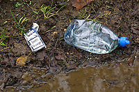 Cigarette packet and plastic bottle discarded by the roadside, Oxfordshire, United Kingdom