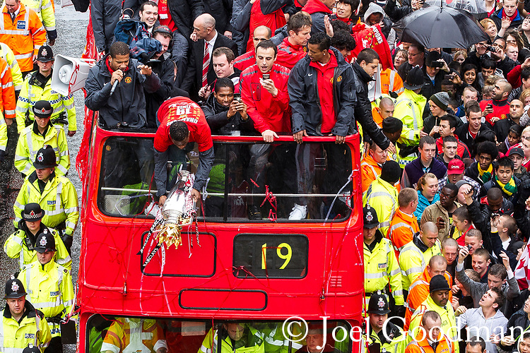 © Joel Goodman - 07973 332324 . 30/05/2011 . Manchester , UK . Manchester United defender Patrice Evra nearly drops the league trophy during an opened top bus parade through Manchester . Fans line Deansgate in Manchester City Centre, as Manchester United Football Club hold an open-topped bus parade through the city. The team are celebrating winning the Premier League title for the nineteenth time . Photo credit : Joel Goodman