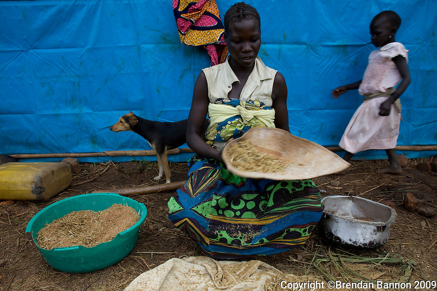 A recently arrived refugee woman sifting millet for the day's meal.