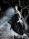 Beautiful young woman wearing classic long black dress in a dark mysterious forest. Digitally composed image.