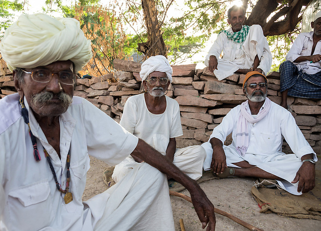 03 September, 2013, Jodhpur, Rajasthan INDIA : Local men sit outside shops at the beginning of a road built under  the Pradhan Mantri Gram Sadak Yojana program (PMGSY)  in Lordi Dejgara village in Rajasthan. PMGSY is a nationwide plan in India to provide good all-weather road connectivity to unconnected villages.<br /> It is under the authority of the Ministry of Rural Development and was begun on 25 December 2000 It is fully funded by the central government and implemented in conjunction with the World Bank<br /> The goal was to provide roads to all villages  with a population of 500 persons and above by 2007, in hill states, tribal and desert area villages with a population of 250 persons and above by 2007. Picture by Graham Crouch/World Bank