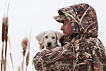 Gun dog trainer Glen Cropper cradles a yellow Labrador puppy.