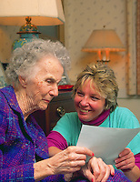 Portrait of a senior woman and smiling caregiver at a nursing home.