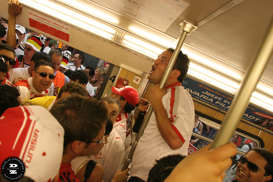Tunisian National Soccer Team fans cheer and wave flags in a jammed-packed subway train in Munich, Germany on Wednesday, June 14th, 2006. The fans were on their way to the Bayern-Munich arena  to watch Tunisia play their FIFA World Cup first round match against Saudi Arabia .  The two teams tied at 2-2.