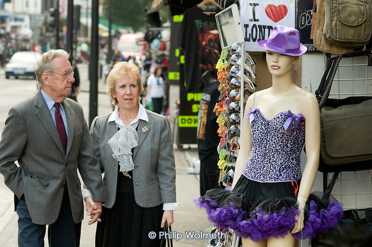 A middle-aged couple passes a display mannequin outside a shop near Camden Lock Market