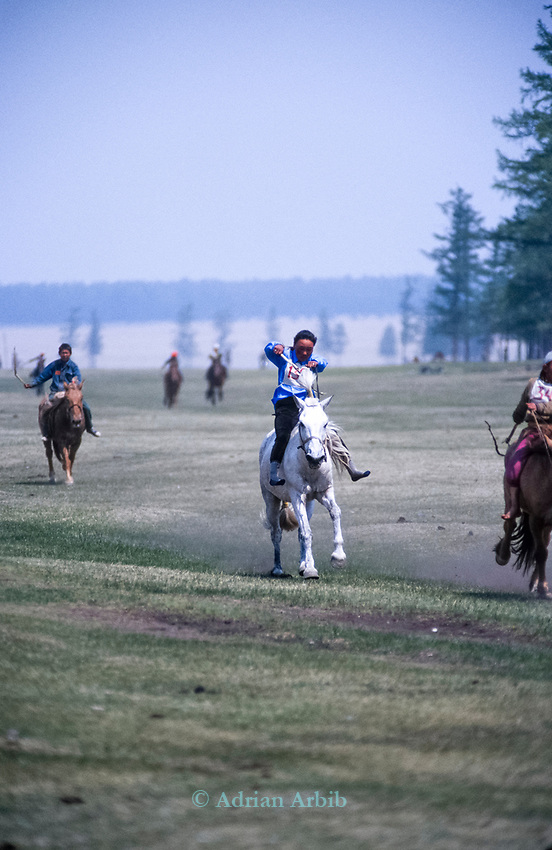 Bareback Horseracing at the Naadam festival.    Northern outer Mongolia<br /> <br /> The games are Mongolian wrestling, horse racing, and archery, and are held throughout the country during midsummer. Women have started participating in the archery and girls in the horse-racing games, but not in Mongolian wrestling.