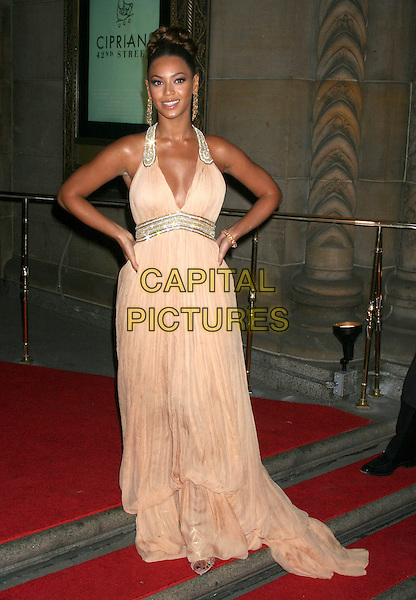 BEYONCE KNOWLES.Attends the AmfAR Gala Honoring John Demsey, Whoopi Goldberg and Bill Roedy at Cipriani, New York, NY, USA..January 31st, 2007.full length silver gold trim earrings halterneck peach dress hands on hips.CAP/IW.©Ian Wilson/Capital Pictures