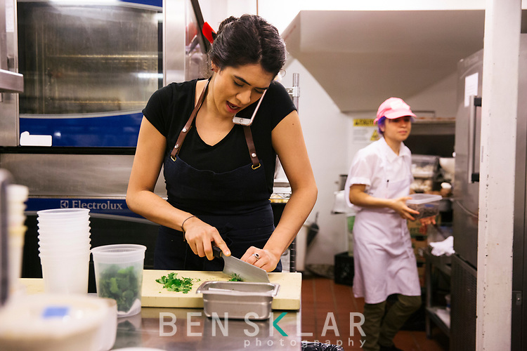 11:37<br /> <br /> Daniela Soto-Innes, chef de cuisine, chops cilantro while fielding phone calls in regards to the sister restaurant downtown, Atla, opening the following day.