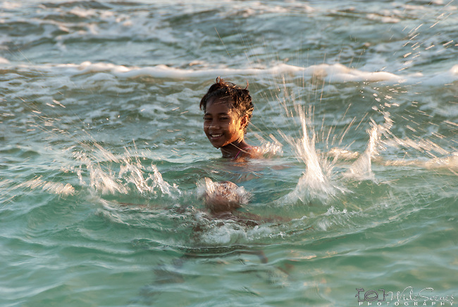 A boy splashing in the sea on Kiritimati island in Kiribati