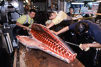 Three men cut a large tuna into smaller pieces for sale, watched by a woman trader in a small cabin at  Tsukiji Wholesale fish market n Tokyo, Japan, April 21st 2006