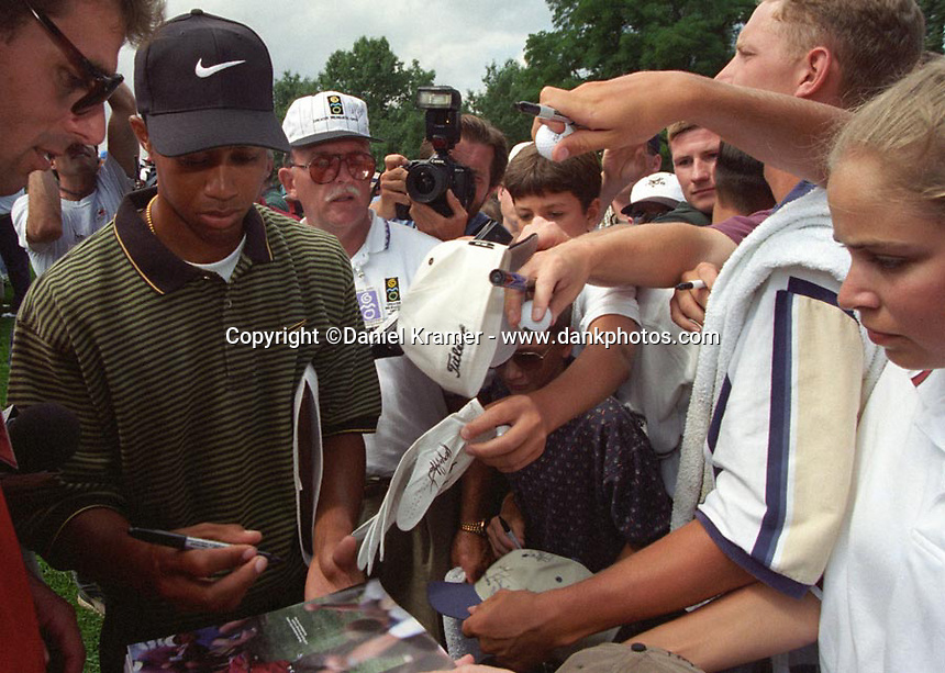 Tiger Woods signs autographs at his first professional golf tournament at the Greater Milwaukee Open in Milwaukee, Wisconsin.