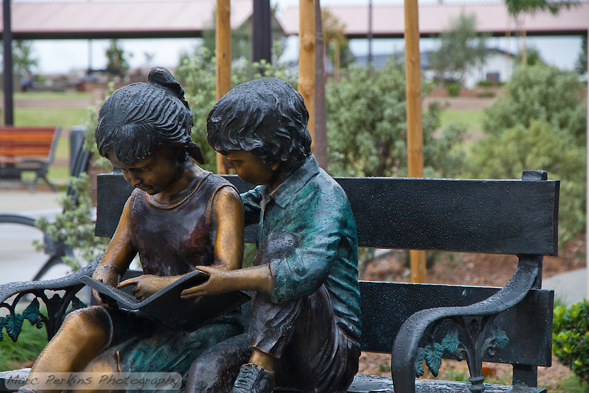 The gorgeous sculpture of two children reading a book on a park bench at Stanton Central Park's children's play area, seen on a rainy day with the picnic pavillion in the background.  The children are covered in raindrops.
