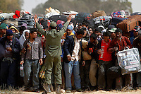 A soldier tries to establish order as refugees reach a camp. Thousands of refugees from Bangladesh walk from the border to a camp in the Tunisian desert. Tens of thousands of people, mainly migrant workers, fled unrest in Libya and crossed the border into Tunisia. Some slept in the open for several days before being processed.  At the same time forces loyal to Col. Gaddafi fought opposition forces in various parts of the country.
