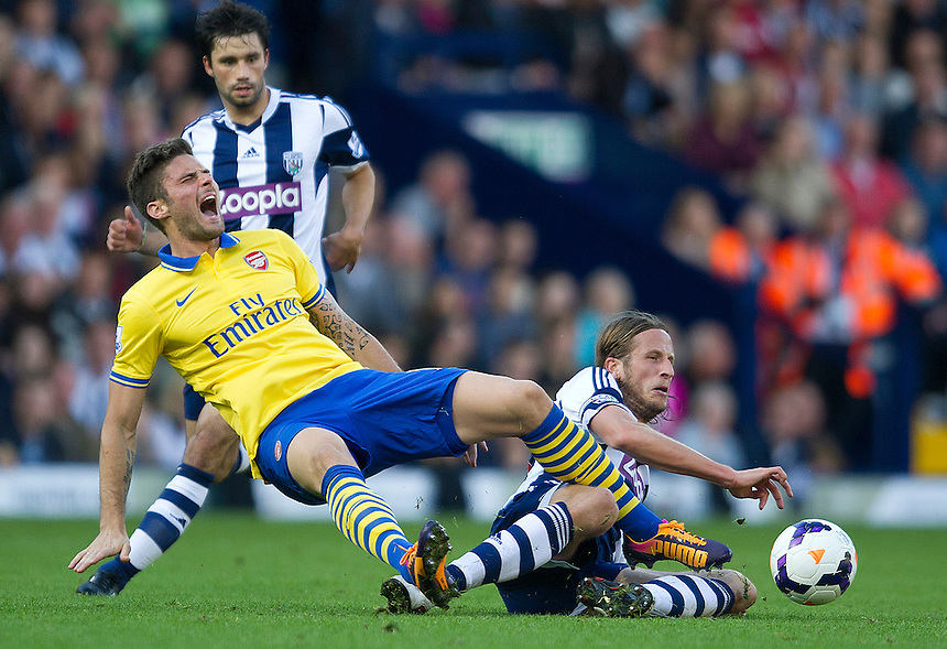 Arsenal's Olivier Giroud shows the pain after this tackle from West Bromwich Albion's Jonas Olsson<br /> <br /> Photo by Stephen White/CameraSport<br /> <br /> Football - Barclays Premiership - West Bromwich albion v Arsenal - Sunday 6th October 2013 - The Hawthorns - West Bromwich<br /> <br /> &copy; CameraSport - 43 Linden Ave. Countesthorpe. Leicester. England. LE8 5PG - Tel: +44 (0) 116 277 4147 - admin@camerasport.com - www.camerasport.com