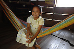 Smiling Mayan girl with dress and barefeet relaxing on the hammock in her thatched hut in the southern Belize village of Midway.