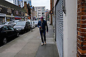 London, UK. 04.04.2015. Man, walking, listening to music, East London. Photograph © Jane Hobson.