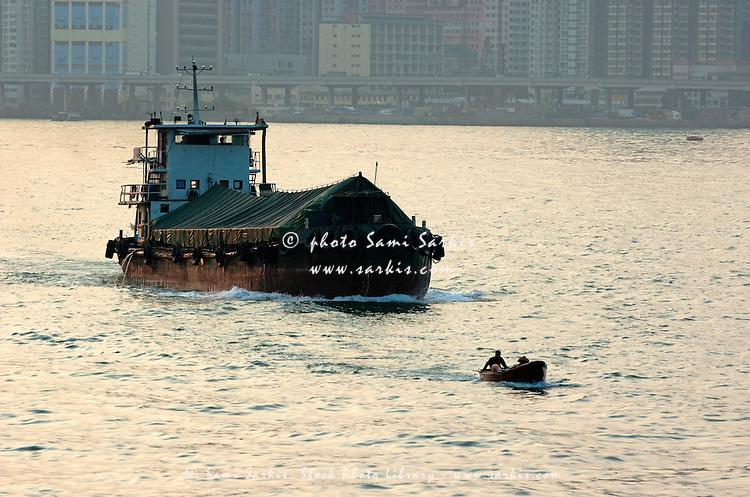 Large barge behind a tiny fishing boat crossing the Victoria Harbor, Hong Kong, China.