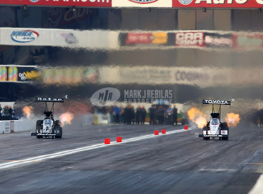 Feb 8, 2014; Pomona, CA, USA; NHRA top fuel dragster driver Spencer Massey (left) races alongside Antron Brown during qualifying for the Winternationals at Auto Club Raceway at Pomona. Mandatory Credit: Mark J. Rebilas-