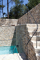 A beautifully crafted natural stone wall surrounds  a courtyard swimming pool