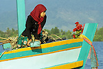 Cham woman wearing red head scarf sitting in prow of colourful fishing boat, dawn on the  Sanke river, Kampot, Cambodia.