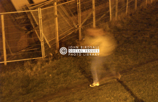 Young man walking past security fence at night,  This estate plagued by vandalism, Tyneside UK