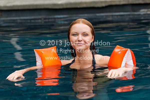 Woman in pool wearing water wings