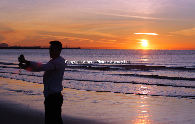 WEATHER PICTURE WALES<br />Pictured: A young man takes a selfie while the sun rises over Swansea Bay in Wales, UK. Wednesday 30 November 2016<br />Re: Low temperatures with sunshine in most parts of the UK