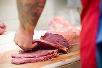 Meat cutter Russ Brown tackles his job in the cutting room of Elias' Butcher Shop in Roanoke Rapids, North Carolina.
