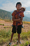 The responsibility of this young man goes far beyond the brother who is on his back.  (Punakha red rice fields, Bhutan)