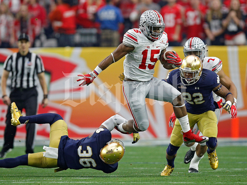 Ohio State Buckeyes running back Ezekiel Elliott (15) jumps past Notre Dame Fighting Irish cornerback Cole Luke (36) in the first quarter during the Fiesta Bowl in the University of Phoenix Stadium on January 1, 2016.  (Dispatch photo by Kyle Robertson)
