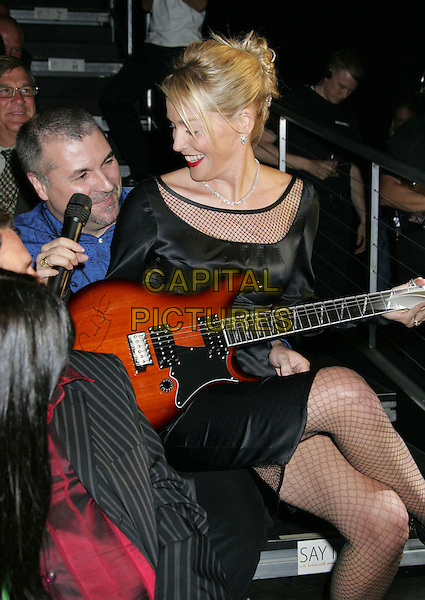 SHARON STONE.Macy's Passport 2006 - Fashion Show and Auction held at Barker Hanger, Santa Monica, California, USA,.28 September 2006..half length black dress fishnet fish net tights guitar sitting on lap.Ref: ADM/RE.www.capitalpictures.com.sales@capitalpictures.com.©Russ Elliot/AdMedia/Capital Pictures.