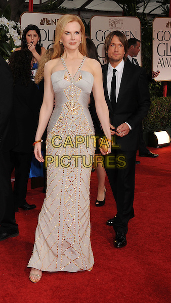 Nicole Kidman (wearing Versace) & Keith Urban (in background).Arrivals at the 69th Annual Golden Globe Awards at The Beverly Hilton Hotel, Beverly Hills, California, USA..January 15th, 2012.globes full length white grey gray dress silver gold beads beaded black suit married husband wife.CAP/GDG.©GDG/Capital Pictures