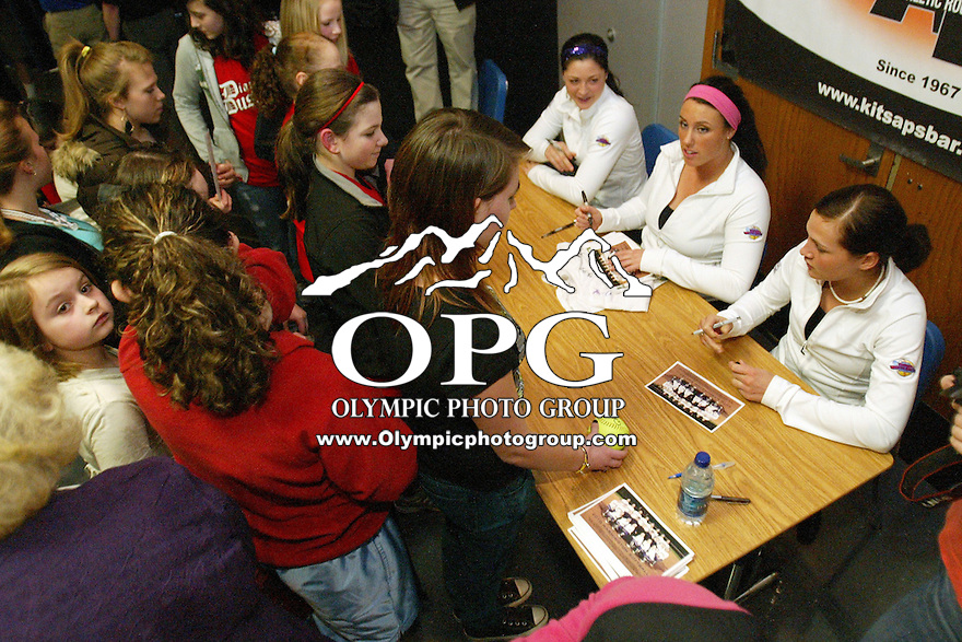 27 January 2010:  Washington Husky softball players (left) Morgan Stuart (center) Danielle Lawrie (right) Alyson McWherter signed autographs for fans during the KCBAR Roundtable SoftballFest.  Members for the Washington Softball team were on hand to give encouragement to students and community members on Wednesday at Olympic High School in Silvedrale, WA about striving for your goals and to make the right choices in life at the KCBAR Roundtable SoftballFest.