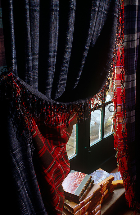 French windows in the study are draped in double-sided curtains made of contrasting tartans of dark blue and red