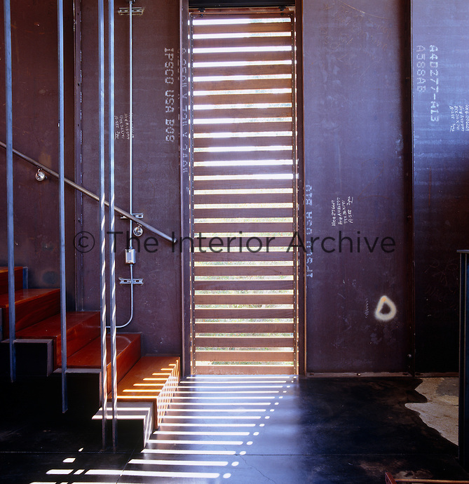Sunlight streams in through a louvered window casting shadows on the floor of the hall