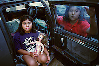 Texas, McAllen, Rio Grande Valley. Migrant workers children playing in their car,  The girl on the right is suffering from depression.