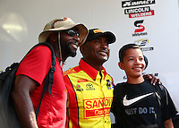 Aug. 2, 2014; Kent, WA, USA; NHRA top fuel dragster driver Antron Brown (center) poses for a photo with fans in the pits during qualifying for the Northwest Nationals at Pacific Raceways. Mandatory Credit: Mark J. Rebilas-USA TODAY Sports