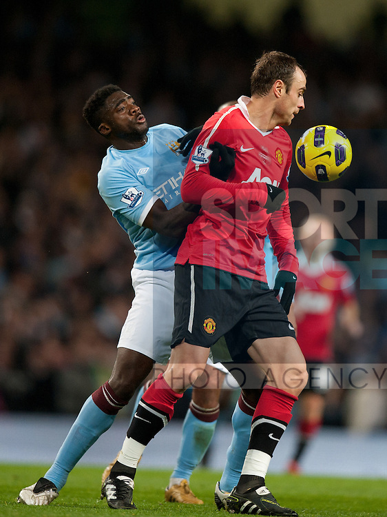 Kolo Toure of Manchester City and Dimitar Berbatov of Manchester United scrap for the ball