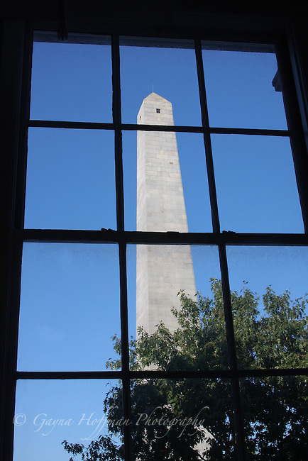 The Bunker Hill Monument viewed through windowpanes of a tall window.