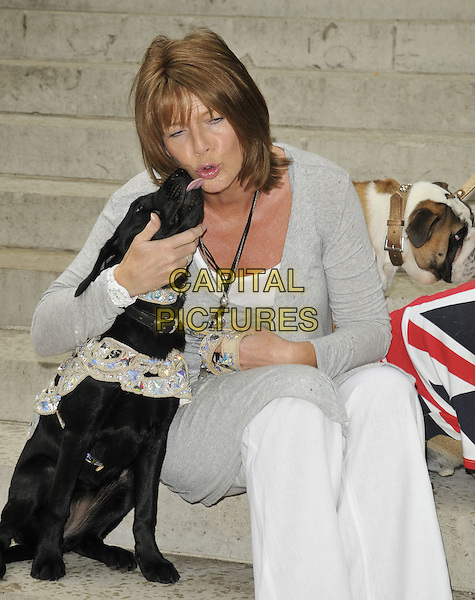 "RUTH LANGSFORD .""Cats & Dogs: Revenge of Kitty Galore"" UK premiere, Holland Park Open Air Theatre, London, England..August 1st, 2010.half 3/4 length animal pet sitting grey gray cardigan white flared trousers kiss kissing funny eyes closed tongue .CAP/CAN.©Can Nguyen/Capital Pictures."