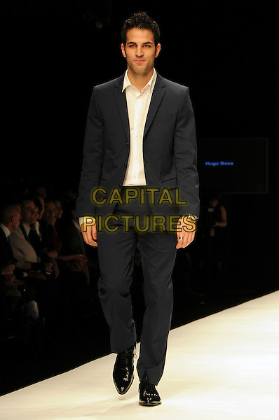 CESC FABREGAS, Arsenal captain .The Fashion For Relief Haiti 2010 show for London Fashion Week Autumn/Winter 2010 at Somerset House, London, England..February 18th, 2010.LFW catwalk runway full length black suit white shirt footballer .CAP/CAS.©Bob Cass/Capital Pictures.