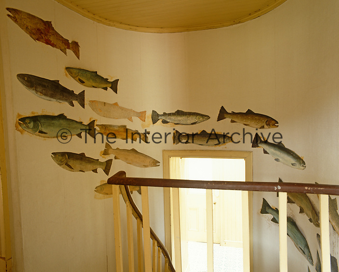 The curved wall of the staircase is decorated with paper cutouts of salmon