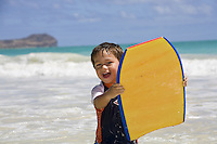 A two-year-old boy holds a bodyboard at Kailua Beach, Oahu, Hawaii.