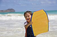 A two-year-old boy holds a bodyboard at Kailua Beach, Oahu, Hawaii.