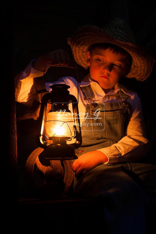 A little farmer boy in the barn with a oil lamp