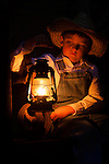 A little farmer boy in the barn with a oil lamp